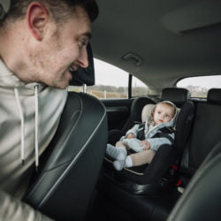 man looking at baby in babyseat