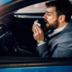 Businessman blowing his nose inside the car
