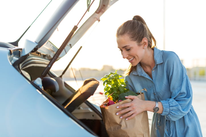 Young woman in car park carrying shopping bag of groceries