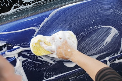 A man washing a car door with a sponge