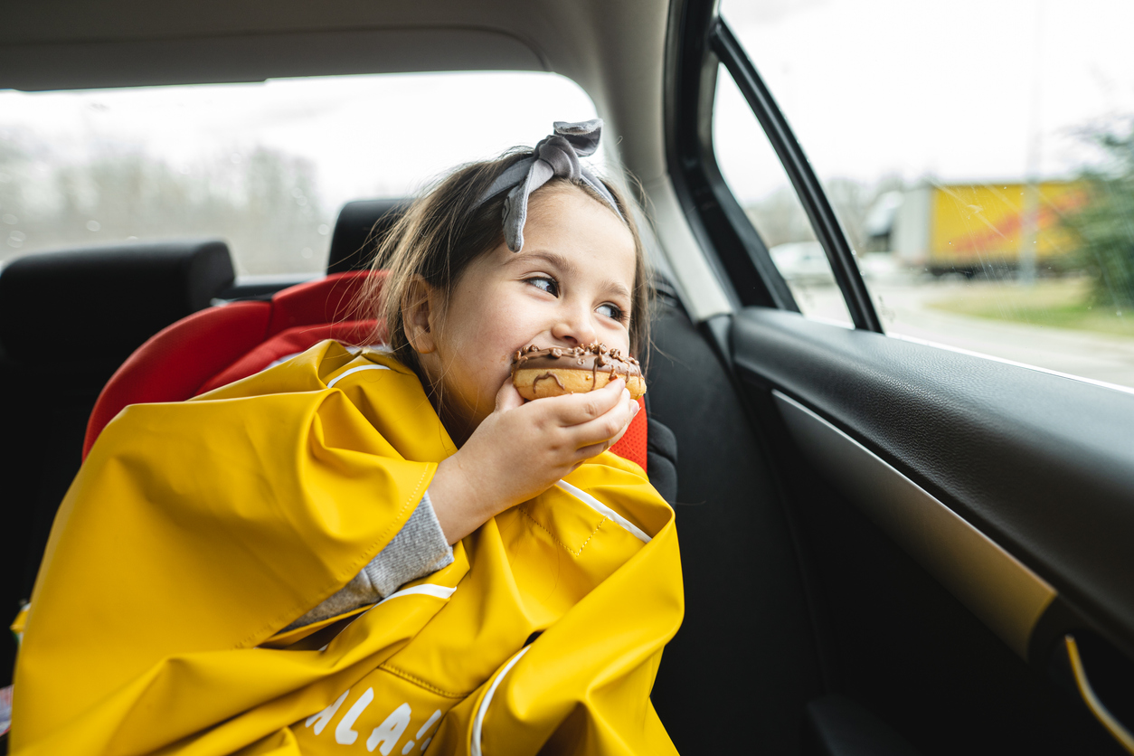 child eating donut in her carseat