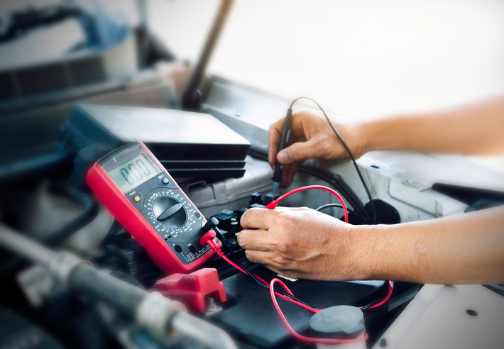 Close up of auto mechanic jumping battery car,check voltage level car battery.