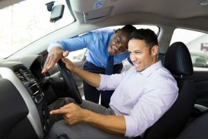 salesman showing new car interior to customer sitting inside the car