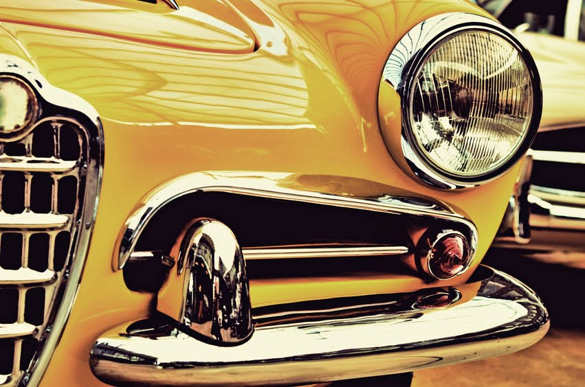 The hood, bumper, headlight and radiator of stylish yellow vintage car. Vintage style. Sophistication. Elegance.