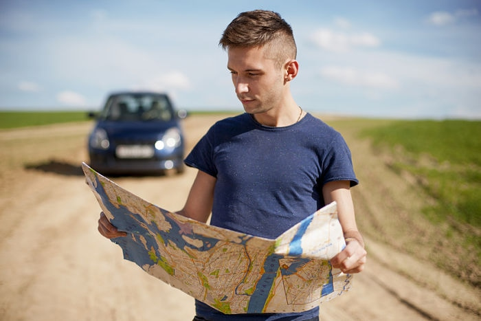 Photo of a traveler parked his car by the side of a road, lost and reading the map. Focus on the map and male.