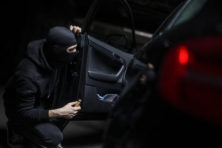 Burglar opening a car door. Unrecognisable caucasian male wearing a balaclava.